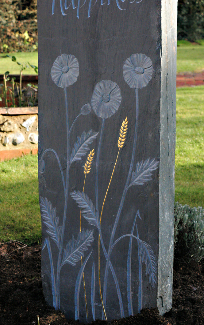 Relief carved flowers and gilded corn on Welsh slate standing stone